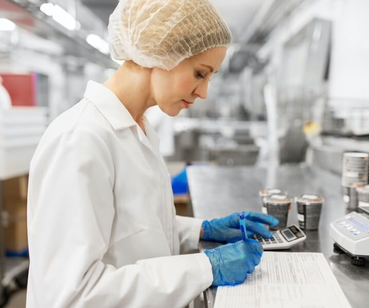 Worker in a lab coat calculating values